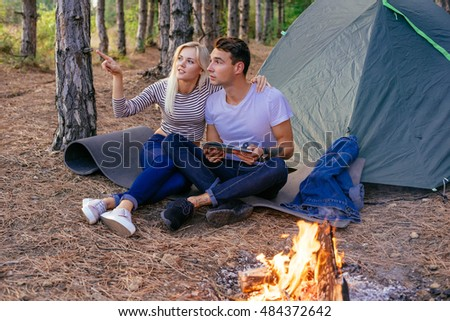 Young caucasian couple camping in the forest. Hikers in the wood near the tent with campfire, ukulele guitar, map and compass.