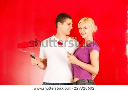 Young caucasian couple having fun painting wall in their new home - stock photo