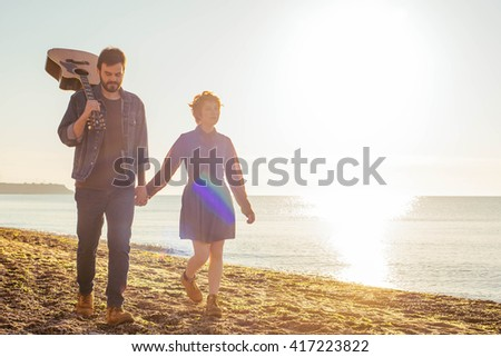 young caucasian couple playing guitar on beach