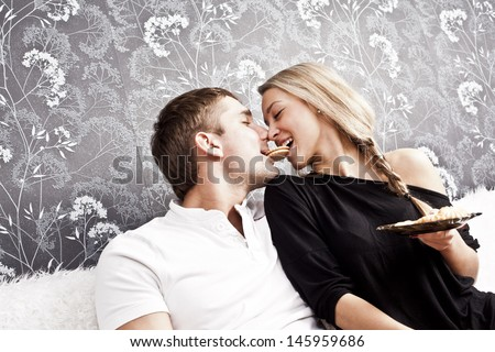 young caucasian couple sitting on a couch together a cookie bite her lips Copy space for inscription  - stock photo