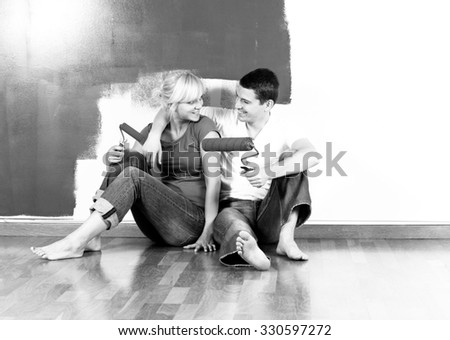 Young caucasian couple sitting on the floor and smiling in front of partially painted wall - black and white, intentionally added grain - stock photo