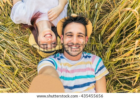Young caucasian couple taking selfie lying on the grass. Two friends having fun outdoor. Smiling on the camera. Concept about people, lifestyle and technology - stock photo
