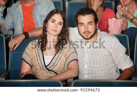 Young caucasian couple watch movie in theater