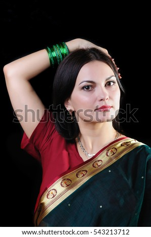 Young caucasian dark-haired pretty woman in traditional indian sari. (Studio low key shot)