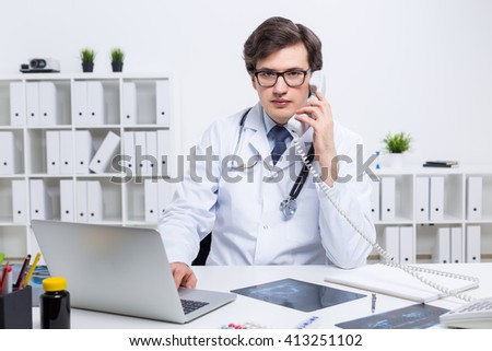 Young caucasian doctor using laptop and having a telephone conversation at his office desk with shelves in the background - stock photo