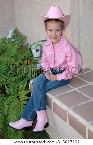 young caucasian elementary school age child in a pink cowgirl outfit excited to be going to her first square dance. Sitting on a tile bench next to green plants - stock photo