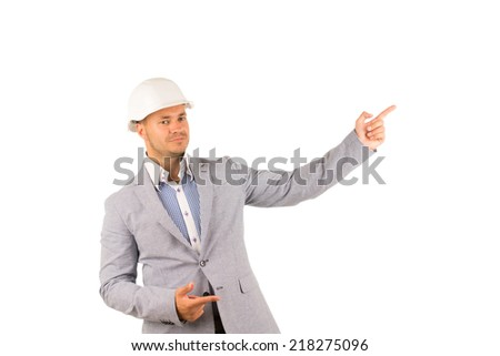 Young Caucasian Engineer on Gray Coat and White Helmet Looking at Camera While Pointing Side. Isolated on White Background. - stock photo