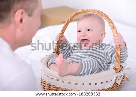 Young Caucasian father playing with baby son at home - stock photo