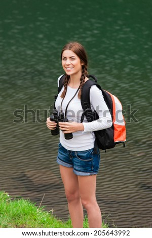 Young caucasian female hiker holding binoculars. Vertical shape.  Glacial Lake on Transfagarasan road, Fagaras Mountains. A lake surrounded by mountain ridges - stock photo