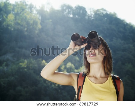 young caucasian female hiker watching through binoculars. Horizontal shape, front view, head and shoulders, copy space - stock photo