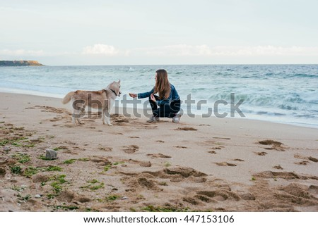 young caucasian female playing with siberian husky dogs on beach