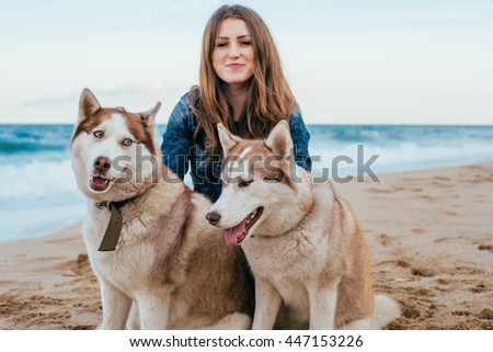 young caucasian female playing with siberian husky dogs on beach - stock photo