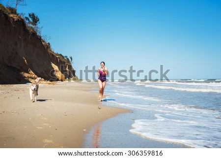 young caucasian female running with husky dogs on beach, girl jogging on seaside with dogs