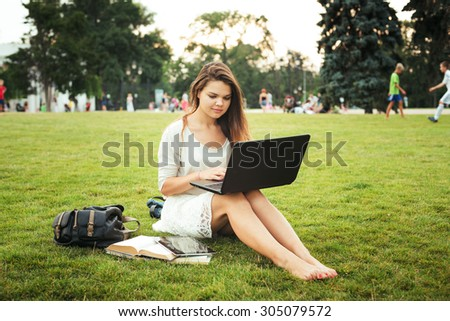 young caucasian female student sitting on a grass in campus area near the university, holding a laptop on her knees. Books, backpack and tablet is around. Student study in campus, education concept
