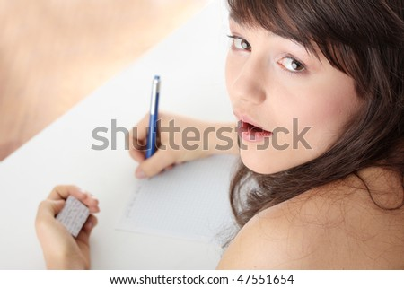 Young caucasian female student stands by school desk and  cheat