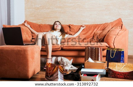 young caucasian female with laptop and shopping bags in living room. Woman tired of shopping. Female and little husky dog after shopping at home