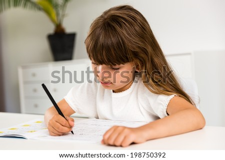 Young caucasian girl doing her homework while sitting at table.