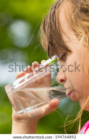 Young caucasian girl drinking from glass with fresh water outdoors during summer time. - stock photo