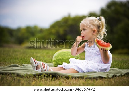 young caucasian girl eating watermodel in the park - stock photo