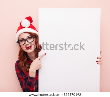 Young caucasian girl in glasses and Hat with white board on pink background.