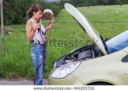 Young caucasian girl putting lipstick in rear-view mirror of a car