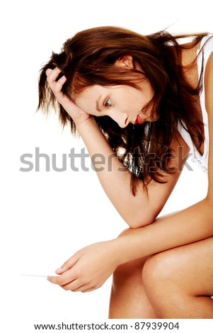 Young caucasian girl sitting and checking her pregnant test over white. - stock photo