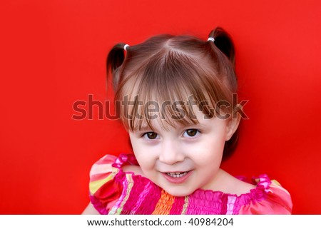Young caucasian girl (2 years old) in pigtails wearing a red and pink plaid dress smiles and looks up. Shot against a red backdrop. - stock photo