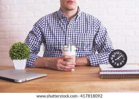 Young caucasian guy with coffee cup in hands sitting at wooden desk with closed laptop, plant and clock. White brick wall in the background - stock photo