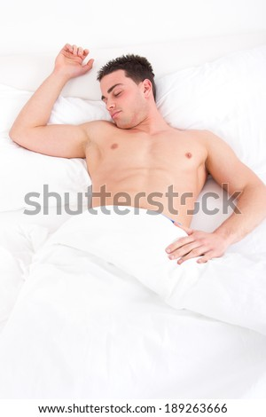 Young caucasian half naked man sleeping in his bed at home with one hand on pillow,  domestic atmosphere. - stock photo