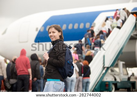 Young Caucasian happy smiling woman passenger in 20s travelling with backpack, boarding airplane, looking at camera, people climbing air stairs on background - stock photo