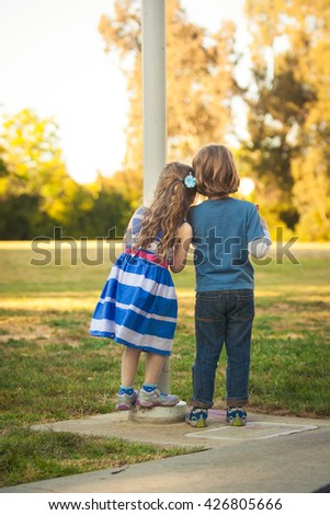 Young Caucasian kids looking on the field during the sunset on a summer day. Also available in horizontal format. - stock photo