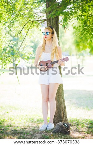 young caucasian long blonde straight hair hippy woman posing leaning against a tree in a city park, playing a ukulele, overlooking, pensive - music, inspiration concept - stock photo