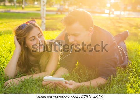Young caucasian lovely couple or college students lying down on the grass together, listening to music. Love, relationship, summer and lifestyle concept