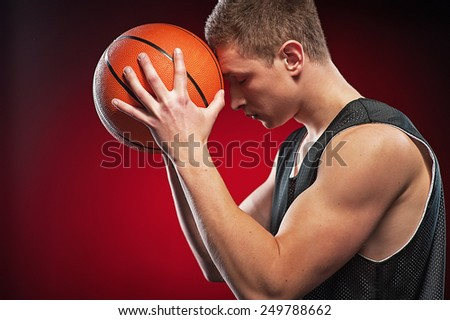 Young Caucasian male basketball player pressing ball to his forehead on red background. Concepts for dreaming of victory - stock photo
