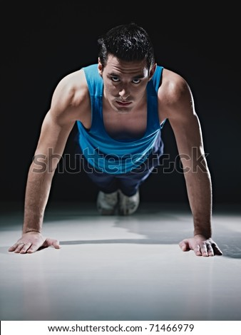 Young caucasian male in sportswear doing push ups on black background. Vertical shape, front view, copy space - stock photo