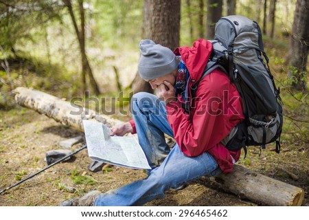young caucasian male with a map in the forest, hiker looking at map outdoors - stock photo
