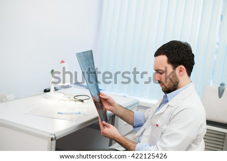 Young caucasian man doctor examines MRI image of human head in office - stock photo