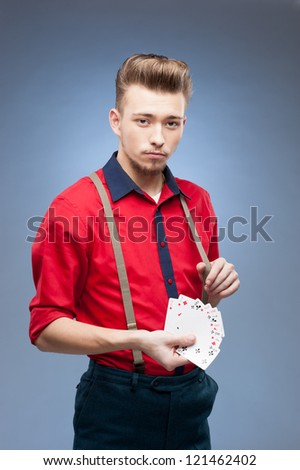young caucasian man in red vintage shirt  holding playing cards - stock photo