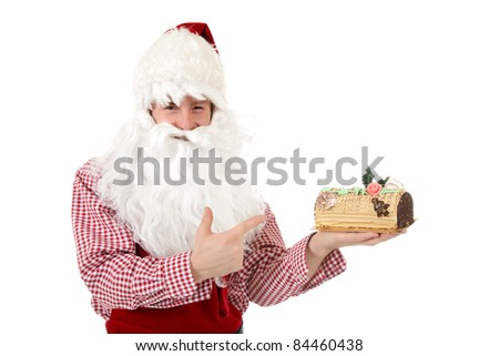 Young caucasian man in Santa Claus clothes pointing at the christmas cake with moca cream and biscuit doug - stock photo