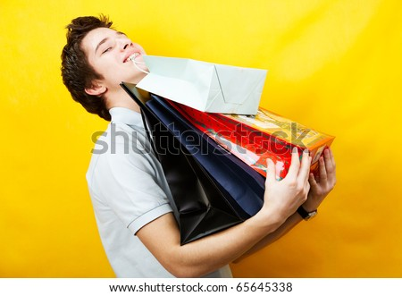 young caucasian man is holding a bunch of shopping bags - stock photo