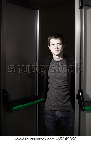 young caucasian man is opening door to the future - stock photo