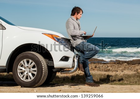 young caucasian man leaning against a pickup truck working on a laptop