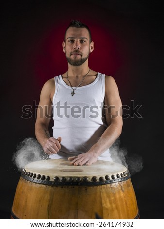 young caucasian man playing drums on old African drums - stock photo
