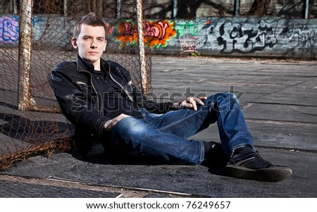 Young caucasian man relaxing near metal football gates - stock photo