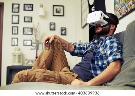 Young Caucasian man resting on comfortable sofa wearing VR headset glasses - stock photo