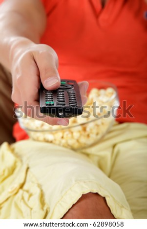 Young caucasian man's hand holding a remote control, popcorn on background. Studio shot. - stock photo