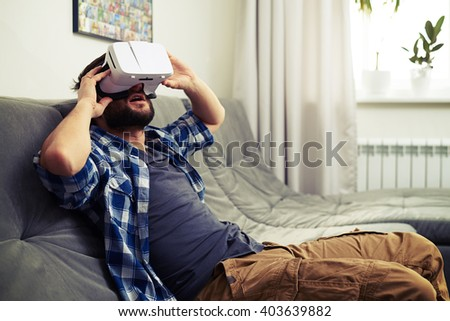 Young Caucasian man sits on sofa and having fun using white VR headset glasses
