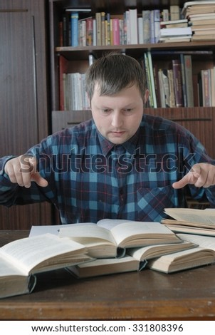 Young caucasian man sitting at the table trying to find some very important for him information in several open books but can't do this. All emotion on his face. - stock photo