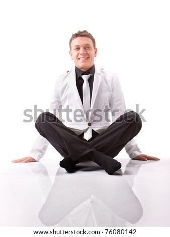 Young caucasian man sitting on white background wearing white and black suit