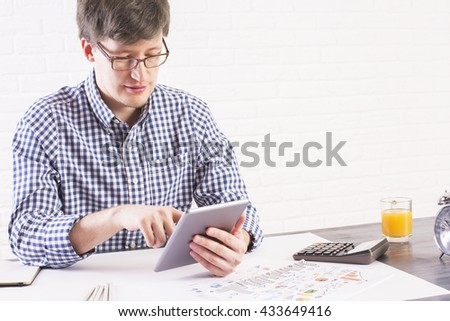 Young caucasian man using tablet at office desk on white brick wall background - stock photo